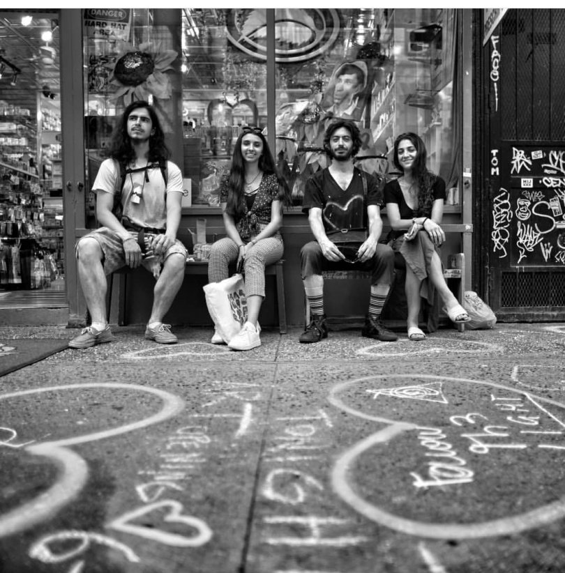 4 artists sitting in front of a store