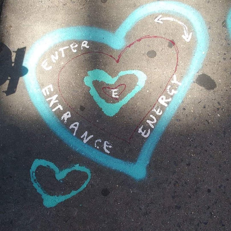 a chalk heart drawn on the side walk in front of Thompson Alchemists