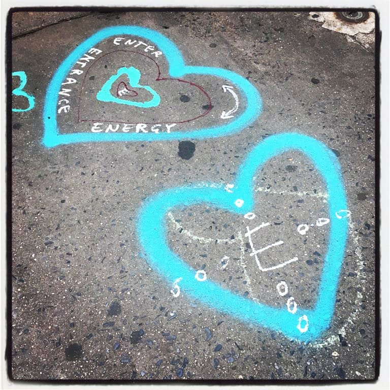 two chalk hearts painted in front of thompson alchemists