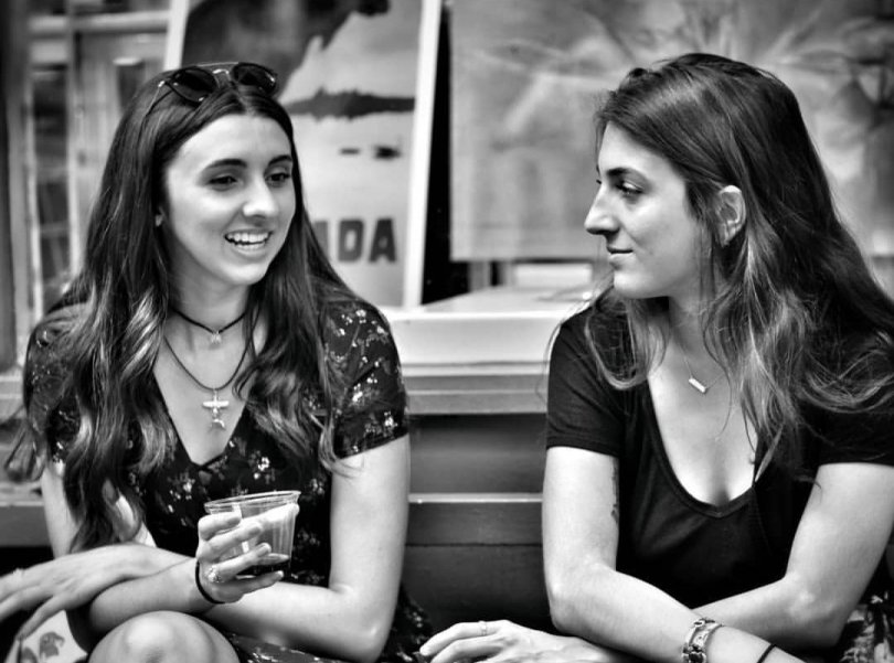 2 female artists sitting on a bench in front of Thompson Alchemists